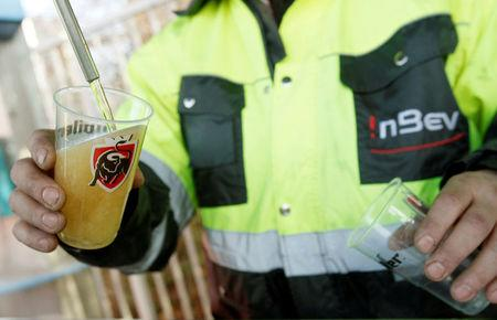 FILE PHOTO: A man serves a beer as Anheuser-Busch InBev workers distribute beer for free at the entrance of the company's plant in Jupille