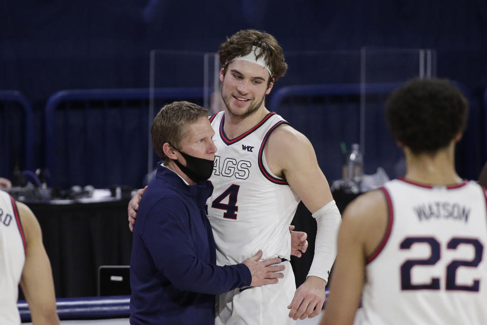Gonzaga coach Mark Few, left, hugs forward Corey Kispert after Kispert, a senior playing his last home game, left the court near the end of the second half of the team's NCAA college basketball game against Loyola Marymount in Spokane, Wash., Saturday, Feb. 27, 2021. Gonzaga won 86-69. (AP Photo/Young Kwak)