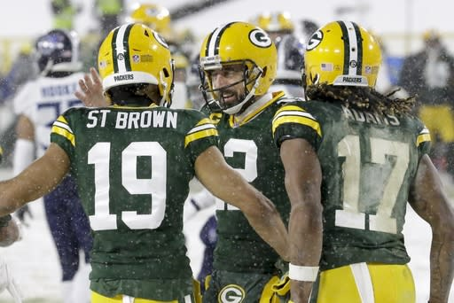 Green Bay Packers' Equanimeous St. Brown celebrates his touchdown catch with Aaron Rodgers (12) and Davante Adams (17) during the first half of an NFL football game against the Tennessee Titans Sunday, Dec. 27, 2020, in Green Bay, Wis. (AP Photo/Mike Roemer)