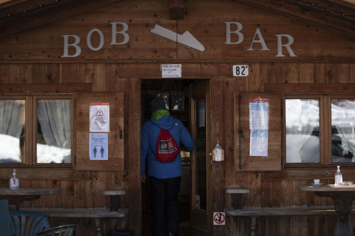 A view of the Bob bar in Cortina d'Ampezzo, Italy, Wednesday, Feb. 17, 2021. When Cortina's century-old bobsled track closed for financial reasons 13 years ago, the adjacent coffee bar kept on serving espressos. Bar owner Costantini pines for the good old days when drivers and brakemen would come whizzing down the track on one side of the café and then hop off their sleds on the other side and come in for a shot of espresso, a vin brulé or perhaps even a taste of the local grappa. (AP Photo/Gabriele Facciotti)