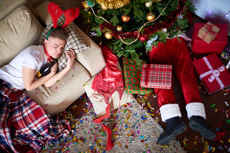 Young man sleeping on the sofa, while drunk Santa Claus sleeping under Christmas tree