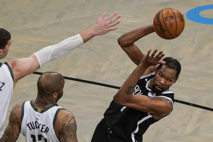 Brooklyn Nets' Kevin Durant, right, passes the ball away from Milwaukee Bucks' P.J. Tucker, center, and Brook Lopez, left, during the first half of Game 7 of a second-round NBA basketball playoff series Saturday, June 19, 2021, in New York. (AP Photo/Frank Franklin II)