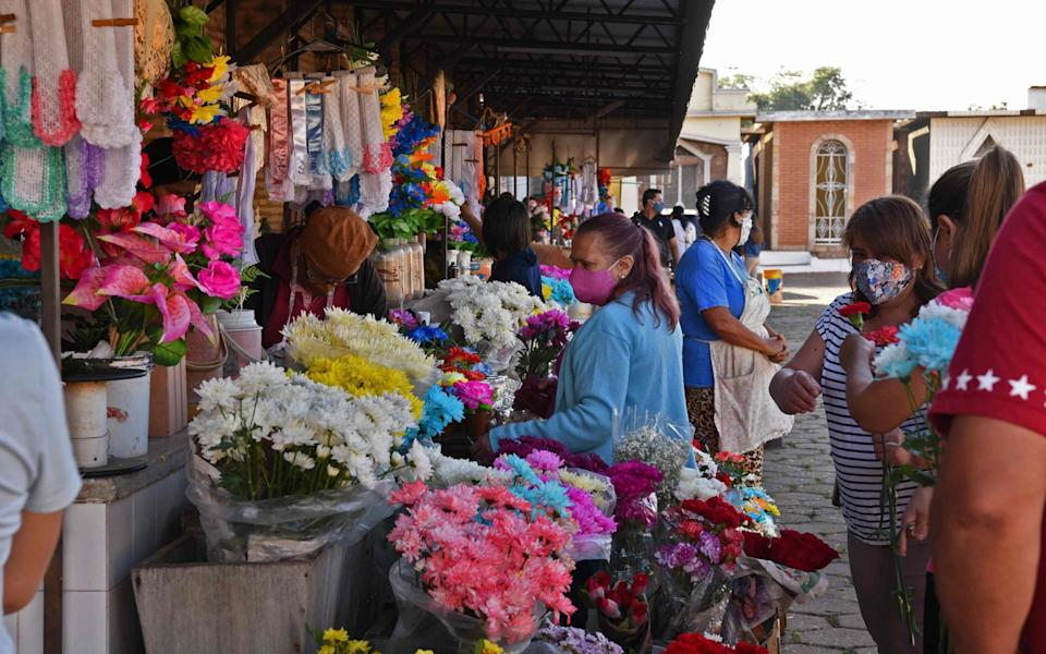 People buy flowers before visiting the tombs of their relatives in Asuncion - Norberto Duarte/AFP
