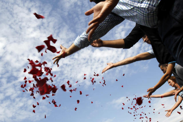 Members of Romania's ethnic Roma minority throw flower petals into Dambovita river during a commemoration ceremony next to the Holocaust Memorial in Bucharest August 2, 2012. Members of the Roma minority commemorated the 68 years since thousands of ethnic Roma people were killed at the Auschwitz-Birkenau concentration camp by Nazi Germany during World War II. REUTERS/Bogdan Cristel (ROMANIA - Tags: SOCIETY ANNIVERSARY)