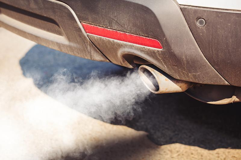 air pollution from dirty and aged vehicle exhaust pipe on road