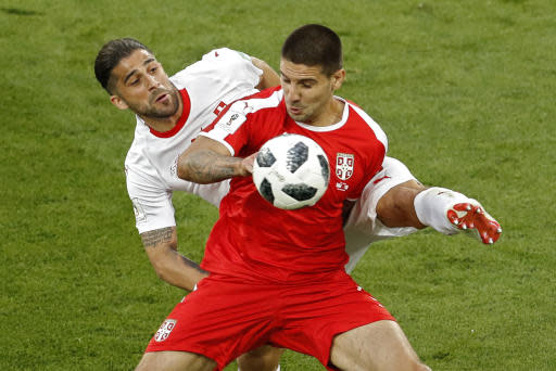 Serbia's Aleksandar Mitrovic, front, battles for a ball with Switzerland's Ricardo Rodriguez during the group E match between Switzerland and Serbia at the 2018 soccer World Cup in the Kaliningrad Stadium in Kaliningrad, Russia, Friday, June 22, 2018. (AP Photo/Antonio Calanni)