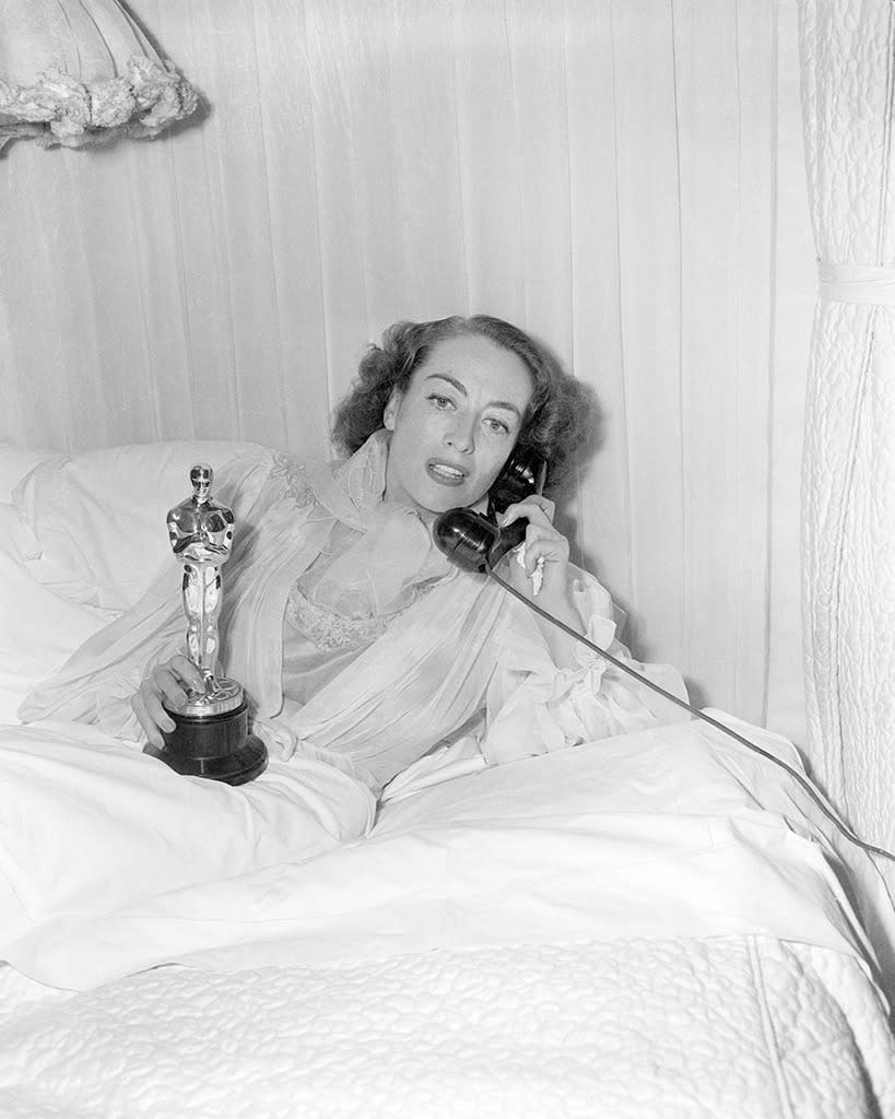 """<p>The fierce <i>Mildred Pierce</i> star called in sick with the flu. If you've seen <i>Mommie Dearest</i>, you know she also called reporters into her bedroom, where she modeled a """"<a href=""""https://news.google.com/newspapers?nid=1243&dat=19460309&id=CN4sAAAAIBAJ&sjid=8R8EAAAAIBAJ&pg=1584,4470189&hl=en"""" rel=""""nofollow noopener"""" target=""""_blank"""" data-ylk=""""slk:fluffy blue nightgown and coffee colored negligee"""" class=""""link rapid-noclick-resp"""">fluffy blue nightgown and coffee colored negligee</a>"""" while monitoring the ceremony, and her eventual win, by radio. </p><p>(Crawford in her bed with Oscar; photo: Getty Images) </p>"""