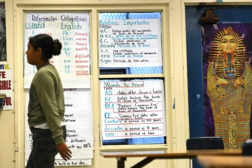 A student at the bilingual Franklin high school in Los Angeles walks past signs bearing lessons in English and Spanish in May 2017