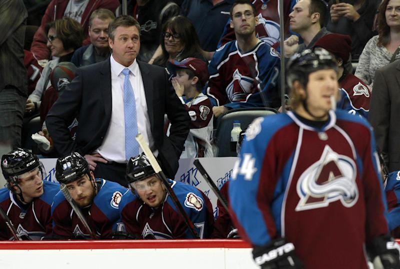 Colorado Avalanche head coach Patrick Roy, back, watches his team in the second period of an NHL hockey game against the Winnipeg Jets in Denver on Sunday, Oct. 27, 2013. (AP Photo/David Zalubowski)