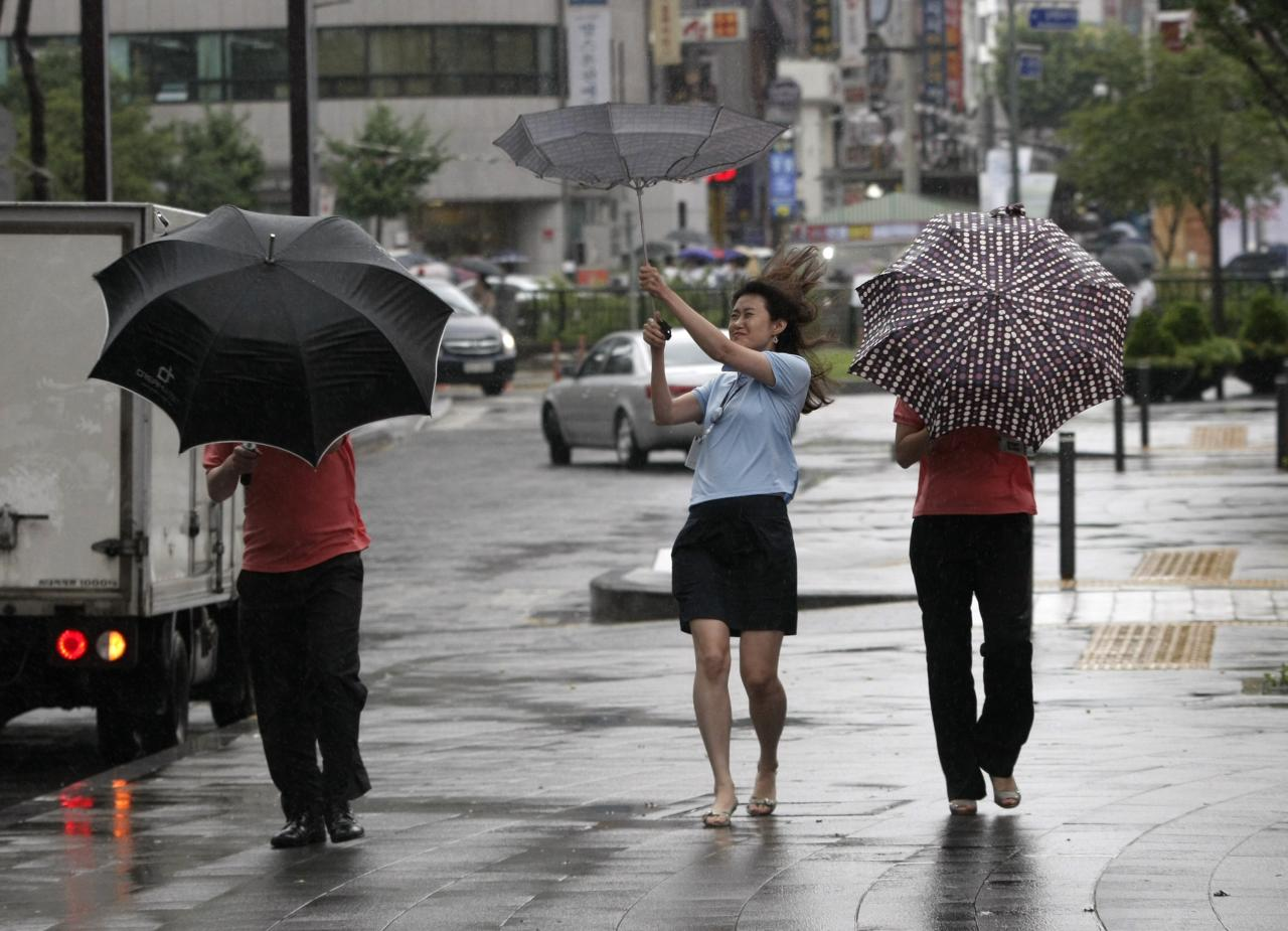 Passers-by try to manage their umbrellas in rain and strong wind in downtown Seoul, South Korea, Monday, Aug. 8, 2011. Typhoon Muifa pounded South Korea's west coast, leaving at least one dead and two others missing as it proceeded northward to reach the capital of Seoul Monday morning, the meteorological office and the emergency control agency said. (AP Photo/Ahn Young-joon)