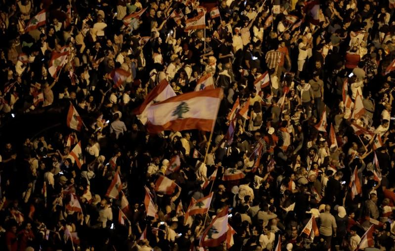 Demonstrators hold Lebanese flags during ongoing anti-government protests in Beirut