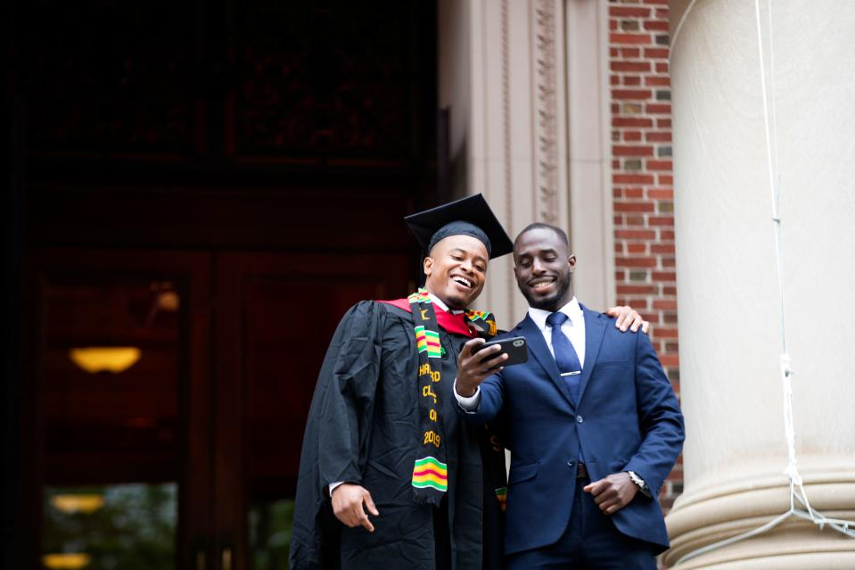 A graduate poses for a selfie during Harvard's 368th commencement ceremony at Harvard University in Cambridge, Massachusetts, on May 30, 2019. (Photo by Allison Dinner / AFP) (Photo credit should read ALLISON DINNER/AFP via Getty Images)
