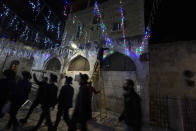 Jewish men walk past Palestinian men stringing colored lights across a main walkway on the eve of the Muslim holy month of Ramadan in the Old City of Jerusalem, Monday, April 12, 2021. (AP Photo/Maya Alleruzzo)