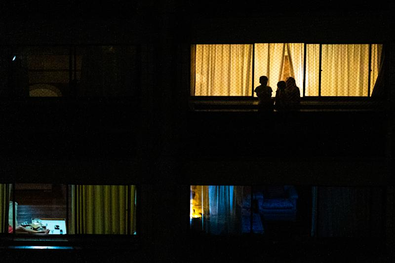 People applaud through their apartment windows honoring health professionals who fight the corona virus during quarantine in Santos, Brazil, March 20, 2020. (Photo by Felipe Beltrame/NurPhoto via Getty Images)