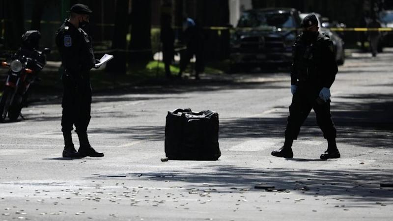 Police officers stand next to bullet casings in the upscale neighbourhood of Lomas de Chapultepec, in Mexico City, Mexico June 26, 2020