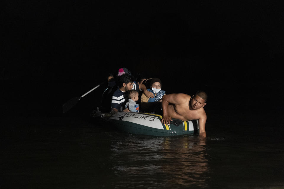 Asylum-seeking migrants' families ride on an inflatable raft to cross the Rio Grande river into the United States from Mexico on April 22, 2021 in Roma, Texas. (Go Nakamura/Getty Images)