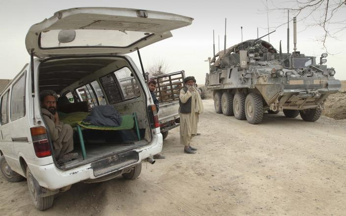 An armored military vehicle from the NATO-led International Security Assistance Force (ISAF) is seen at right, as the covered body of a person who was allegedly killed by a U.S. service member is seen inside a minibus in Panjwai, Kandahar province south of Kabul, Afghanistan, Sunday, March 11, 2012. A U.S. service member walked out of a base in southern Afghanistan before dawn Sunday and started shooting Afghan civilians, according to villagers and Afghan and NATO officials. Villagers showed an Associated Press photographer 15 bodies, including women and children, and alleged they were killed by the American. (AP Photo/Allauddin Khan)