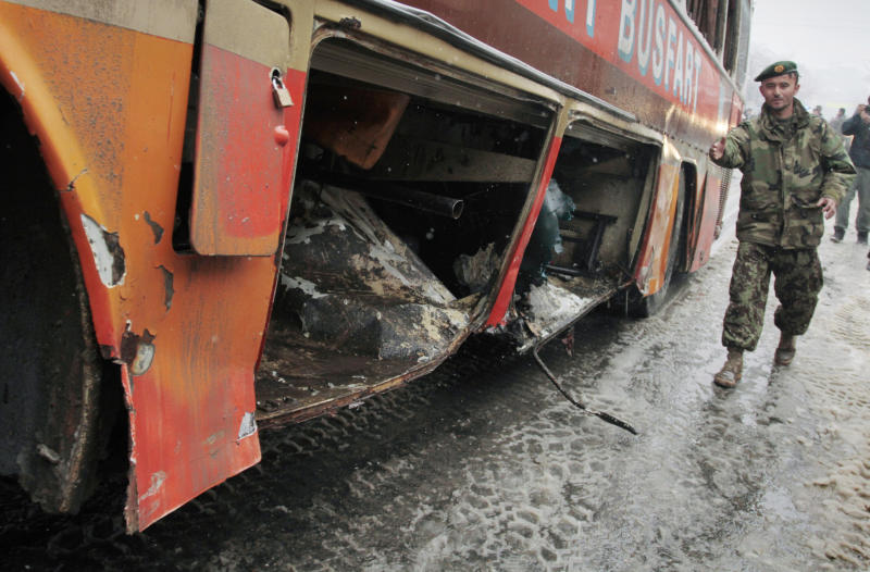 An Afghan soldier walks by a damaged bus being pulled by a crane following a suicide attack in Kabul, Afghanistan, Wednesday, Feb. 27, 2013. A man wearing a black overcoat and carrying an umbrella as a shelter against the heavy snow crossed a street in the Afghan capital early Wednesday morning toward an idling bus filled with Afghan soldiers, where he laid down and wiggled underneath. Then he exploded, engulfing the undercarriage of the bus in flames. (AP Photo/Musadeq Sadeq)