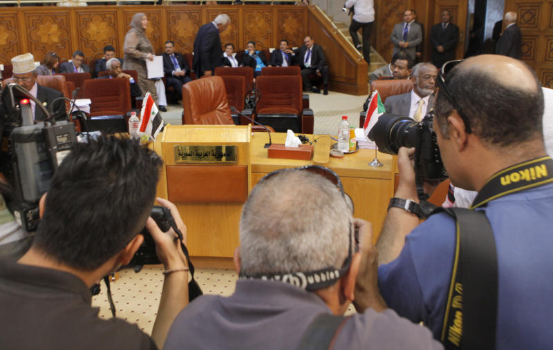 Cameramen document the Syrian delegation's empty chairs during the Arab League's ministerial council meeting at the Arab League headquarters in Cairo, Egypt, Wednesday, Sept. 5, 2012. Egyptian President Mohammed Morsi said during the meeting that Syrian leader Bashar Assad must learn from 'recent history' and step down before it is too late. (AP Photo/Amr Nabil)