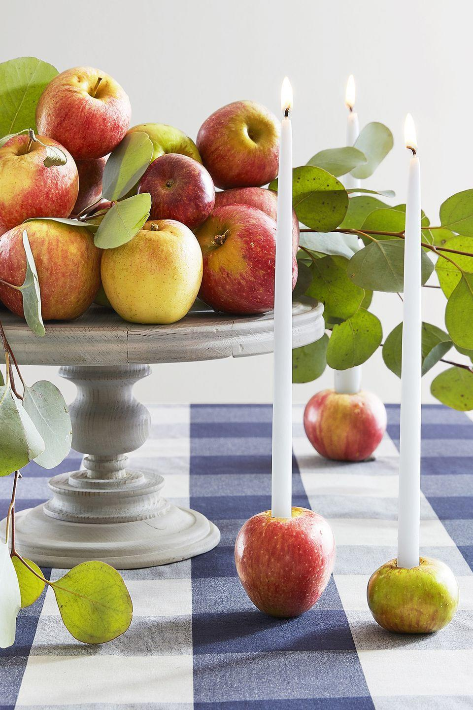 """<p>Utilize your latest farmer's market finds to make this fast display. Use a paring knife to cut a 1-inch-deep hole in the top of a few apples, slightly narrower than the candles, and wedge the candles in. Display alone or with stacked apples and seeded eucalyptus on a neutral cake stand.</p><p><a class=""""link rapid-noclick-resp"""" href=""""https://www.amazon.com/Bolsius-inch-White-taper-candles/dp/B01F49FITE/?tag=syn-yahoo-20&ascsubtag=%5Bartid%7C10050.g.2130%5Bsrc%7Cyahoo-us"""" rel=""""nofollow noopener"""" target=""""_blank"""" data-ylk=""""slk:SHOP TAPER CANDLES"""">SHOP TAPER CANDLES</a></p>"""