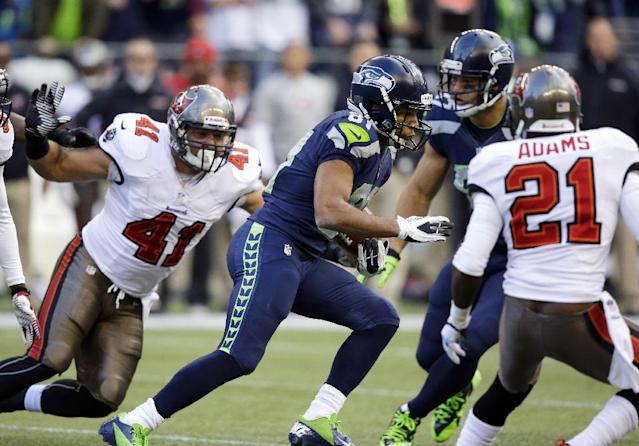 Seattle Seahawks put returner Golden Tate (81) avoids Tampa Bay Buccaneers' Erik Lorig (41) and Michael Adams (21) as he makes a 71-yard punt return in the second half of an NFL football game Sunday, Nov. 3, 2013, in Seattle. (AP Photo/Elaine Thompson)
