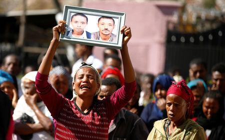 A woman carries a photograph as she mourns her family members suspected to be missing following a landslide when a mound of trash collapsed on an informal settlement at the Koshe garbage dump in Ethiopia's capital Addis Ababa