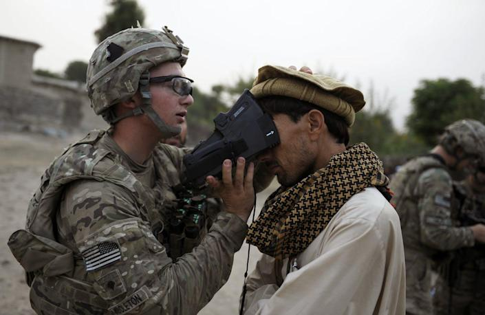"""<span class=""""caption"""">A U.S. Army soldier scans the irises of an Afghan civilian in 2012 as part of an effort by the military to collect biometric information from much of the Afghan population.</span> <span class=""""attribution""""><a class=""""link rapid-noclick-resp"""" href=""""https://www.gettyimages.com/detail/news-photo/an-american-isaf-solider-from-team-apache-of-task-force-news-photo/149781425"""" rel=""""nofollow noopener"""" target=""""_blank"""" data-ylk=""""slk:Jose Cabezas/AFP via GettyImages"""">Jose Cabezas/AFP via GettyImages</a></span>"""