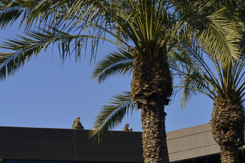 SWAT police officers inspect the roof of an office building after a shooting at the building in Phoenix on Wednesday, Jan. 30, 2013. A gunman opened fire at the Phoenix office building, wounding three people, one of them critically, authorities said. Police were searching for the shooter. (AP Photo/Patrick Sison)