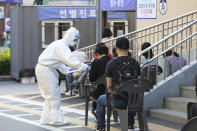 A health official wearing protective gear gives surveys to people waiting for the COVID-19 test at a public health center in Goyang, South Korea, Thursday, May 28, 2020. South Korea on Thursday reported its biggest jump in coronavirus cases in more than 50 days, a setback that could erase some of the hard-won gains that have made it a model for the rest of the world. (AP Photo/Ahn Young-joon)