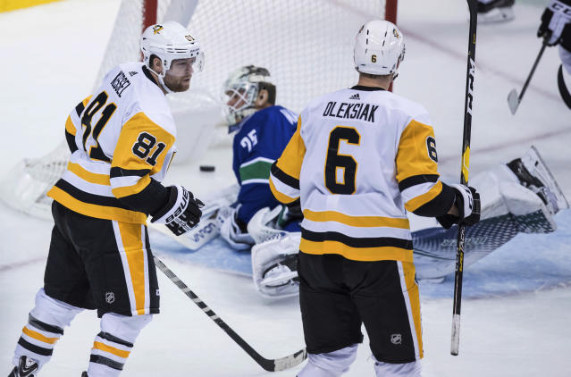 Pittsburgh Penguins' Phil Kessel (81) and Jamie Oleksiak (6) celebrate Kessel's goal against Vancouver Canucks goalie Jacob Markstrom, of Sweden, during the second period of an NHL hockey game in Vancouver, British Columbia, Saturday, Oct. 27, 2018. (Darryl Dyck/The Canadian Press via AP)