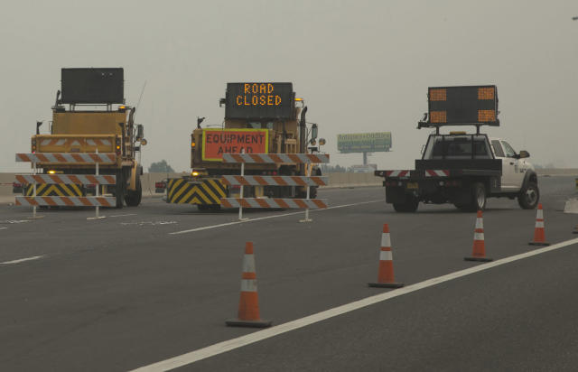 <p>Oregon Department of Transportation vehicles block Interstate 84 at Troutdale, Ore., Sept. 5, 2017 as smoke hangs in the air of a seven-square mile (18-square kilometers) fire that started Saturday. (Photo: Chris Pietsch/The Register-Guard via AP) </p>