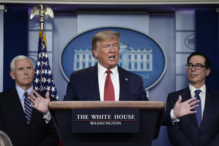 President Trump, flanked by Vice President Mike Pence and Treasury Secretary Steven Mnuchin, speaks during a coronavirus briefing on Wednesday. (Drew Angerer/Getty Images)