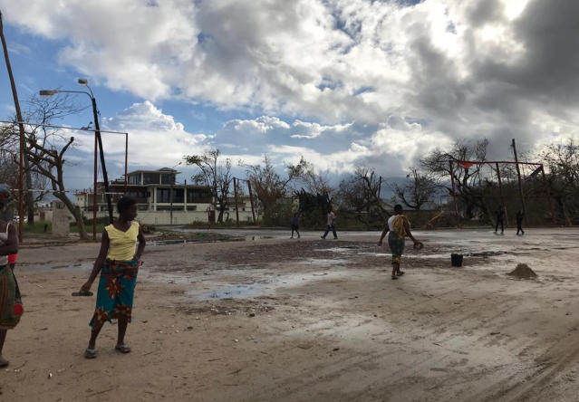 People go on their morning errands amid the shattered city of Beira, Friday, March 22 2019. Some hundreds of people are dead, many more still missing and with many thousands at risk from massive flooding in Mozambique, Malawi and Zimbabwe caused by Cyclone Idai. (AP Photo/Cara Anna)