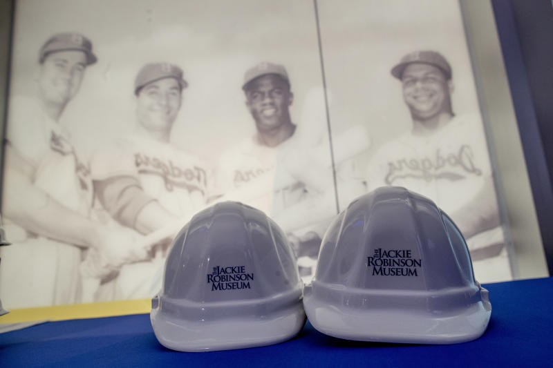 Hard hats used in during the ceremonial ground breaking for the Jackie Robinson Museum are framed by a giant photo of Jackie Robinson, Thursday, April 27, 2017, in New York. (AP Photo/Mary Altaffer)
