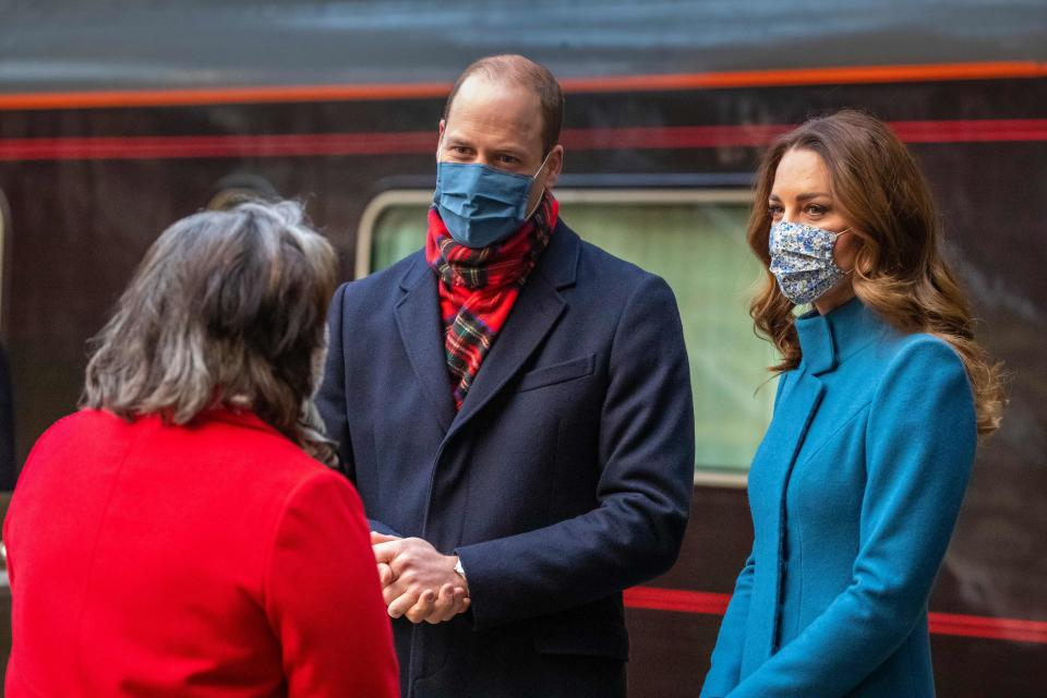 Britain's Prince William, Duke of Cambridge (C) and Britain's Catherine, Duchess of Cambridge (R) speak with Deputy Lord Lieutenant Sandra Cumming (L) after disembarking the Royal train as they arrive at Edinburgh Waverley station for a visit to the Scottish Ambulance Service in Newbridge, Edinburgh in Scotland  on December 7, 2020, on their first full day of engagements on their tour of the UK. - During their trip, their Royal Highnesses hope to pay tribute to individuals, organisations and initiatives across the country that have gone above and beyond to support their local communities this year. (Photo by Andy BARR / POOL / AFP) (Photo by ANDY BARR/POOL/AFP via Getty Images)