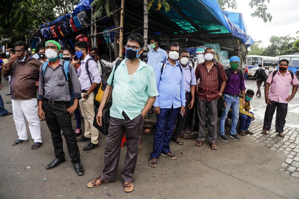 People wearing face masks wait for transport outside a bus station in Kolkata, India, Friday, Aug. 14, 2020. India's coronavirus death toll overtook Britain's to become the fourth-highest in the world with another single-day record increase in cases Friday. (AP Photo/Bikas Das)
