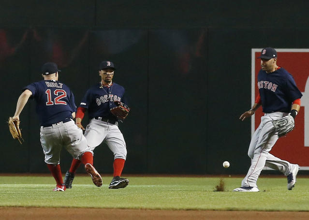 Boston Red Sox's second baseman Brock Holt (12), center fielder Mookie Betts, center, and right fielder J.D. Martinez, right, are unable to track down a pop fly single hit by Arizona Diamondbacks' Zack Godley during the fourth inning of an opening day baseball game Friday, April 5, 2019, in Phoenix. (AP Photo/Ross D. Franklin)