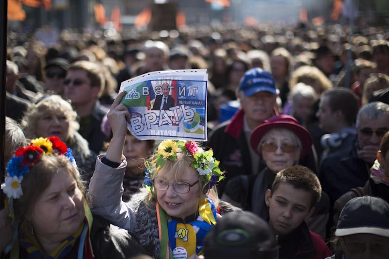 """A woman, wearing a traditional Ukrainian wreath of flowers on her head, holds up a sign with President Vladimir Putin's picture and the words: """"Stop lying!"""" during a rally against pro-Putin media in Moscow, Russia, Sunday, April 13, 2014. More than 10,000 people have turned out in Moscow for an anti-Kremlin rally to denounce Russian state television's news coverage, particularly of the crisis in neighboring Ukraine. (AP Photo/Alexander Zemlianichenko)"""