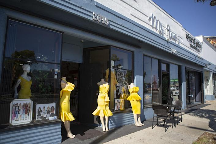 Mannequins in yellow dresses in the window of a storefront and on the sidewalk near the door