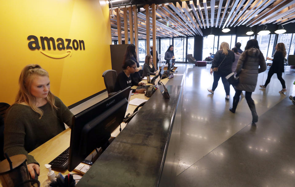 Employees walk through a lobby at Amazon's headquarters Tuesday, Nov. 13, 2018, in Seattle. Amazon, which is growing too big for its Seattle hometown, is spreading out to the East Coast. The online shopping giant ended its 14-month-long competition for a second headquarters Tuesday by selecting New York and Arlington, Va., as the joint winners. (AP Photo/Elaine Thompson)