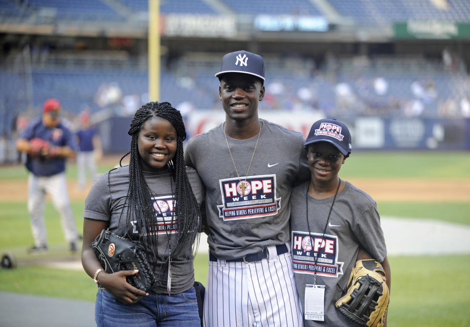 FILE - In this Monday, Aug. 17, 2017, Chris Singleton poses with his sister, Camryn, left, and his brother, Caleb, right, before the New York Yankees and Minnesota Twins baseball game at Yankee Stadium in New York. The Chicago Cubs have drafted Chris Singleton, whose mother was among those killed two years ago during the shooting inside a South Carolina church. Singleton was selected Wednesday by the defending World Series champions with the final pick of the 19th round, No. 585 overall. He is a right-handed-hitting center fielder at Charleston Southern University. (AP Photo/Bill Kostroun, File)