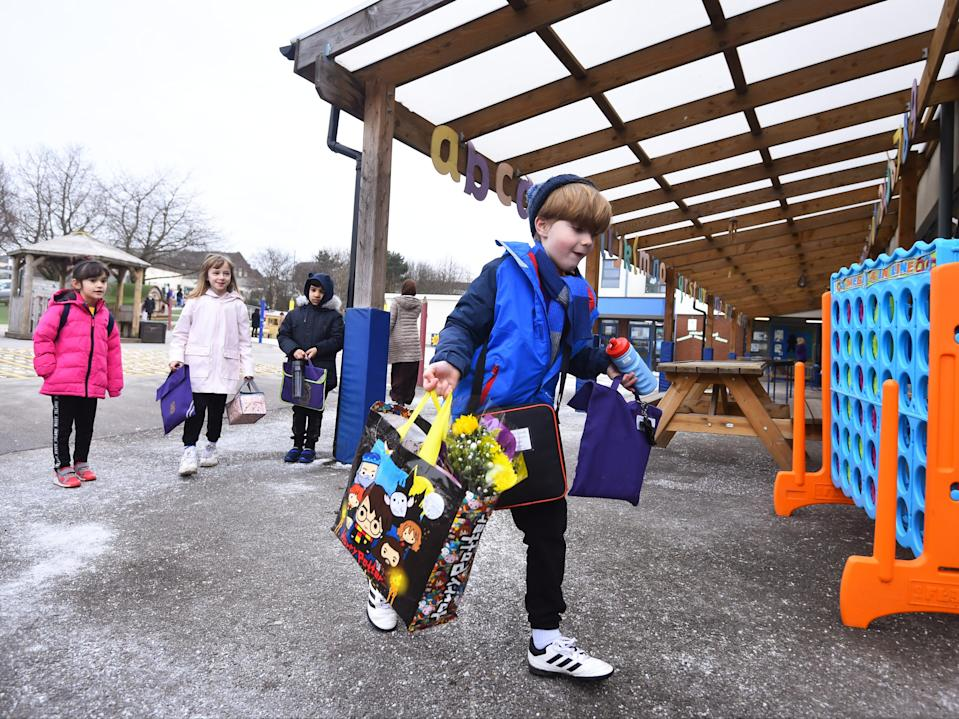 A boy arrives at St Mary's CE Primary School with gifts for his teacher on 8 March 2021 in Stoke on Trent (Getty)
