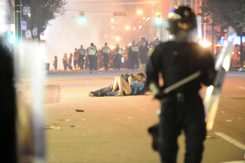 Riot police walk in the street as a couple kisses on June 15, 2011 in Vancouver, Canada. Vancouver broke out in riots after their hockey team the Vancouver Canucks lost in Game Seven of the Stanley Cup Finals. (Photo by Rich Lam/Getty Images)