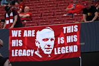 Two Liverpool fans hang a banner remembering former Liverpool's manager Bill Shankly (Photo by Paul ELLIS / AFP)
