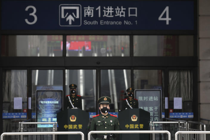 FILE - In this Jan. 23, 2020, file photo, paramilitary police stand guard outside the closed Hankou Railway Station in Wuhan in central China's Hubei Province. A 10-member team of international researchers from the World Health Organization hopes to find clues as to the origin of the coronavirus pandemic in the central Chinese city of Wuhan where the virus was first detected in late 2019. (Chinatopix via AP, File)