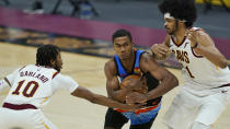 Oklahoma City Thunder's Theo Maledon, center, drives between Cleveland Cavaliers' Darius Garland, left, and Jarrett Allen in the second half of an NBA basketball game, Sunday, Feb. 21, 2021, in Cleveland. (AP Photo/Tony Dejak)