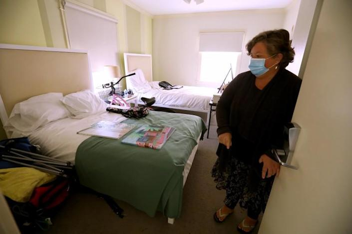 "Wendy Brown enters her room at the Cadillac Hotel in Venice on June 1 as part of Project Roomkey. <span class=""copyright"">(Genaro Molina/Los Angeles Times)</span>"