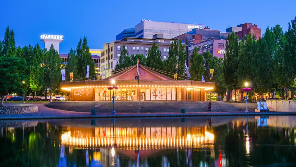 """Spokane, United States - July 21, 2012: People mill around outside the 1909 Looff Carousel, which is seen along the Spokane River with the downtown district of Spokane in the distance."