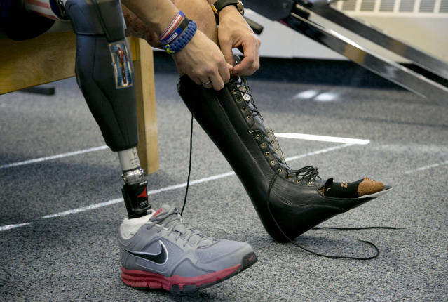 In this Thursday, April 3, 2014 photo, Boston Marathon bombing survivor Marc Fucarile, of Reading, Mass., ties laces on a support for his left leg after rehabilitation exercises at Spaulding Outpatient Center in Peabody, Mass. Fucarile lost his right leg in an explosion near the finish line of the 2013 race. (AP Photo/Steven Senne)