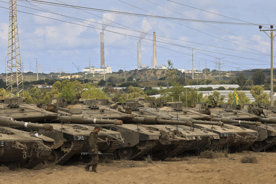An Israeli soldier walks in a staging ground near the border with Gaza Strip, southern Israel, Friday, May 21, 2021. A cease-fire took effect early Friday after 11 days of heavy fighting between Israel and Gaza's militant Hamas rulers that was ignited by protests and clashes in Jerusalem. (AP Photo/Tsafrir Abayov)
